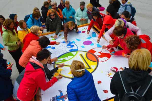 Udeleženci rišejo po velikem platnu slikarske delavnice team building programa